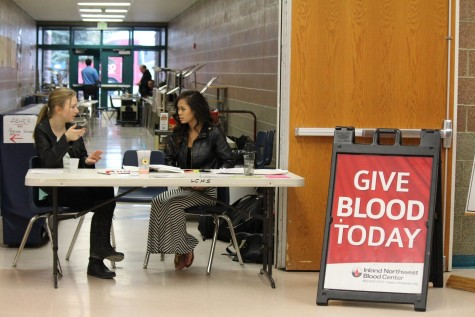 Riley Severs (left) and Chrissy Oka (right) chat as they man the blood drive check-in station.