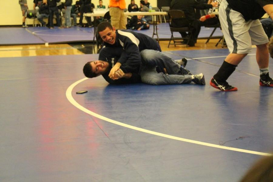 Coach+Corey+Owen+and+senior+Corey+Cook+wrestle+in+their+free+time+at+a+past+tournament.+